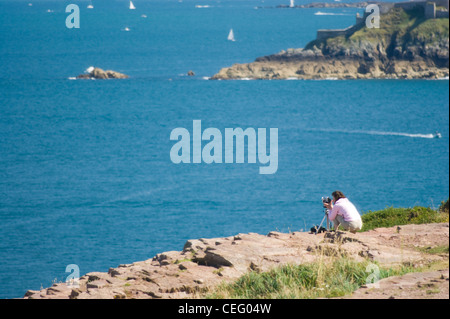 camera operator, cameraman in nature taking pictures a beautiful sea. A young woman is using a video camera to record. - Stock Photo