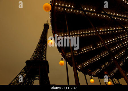 Evening at the Eiffel tour with carousel turning at the basement; Paris, France - Stock Photo