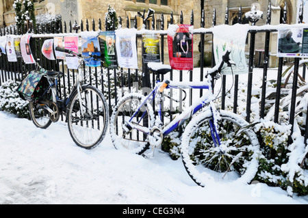 Bicycles and Posters in The Snow, Cambridge, England, UK - Stock Photo