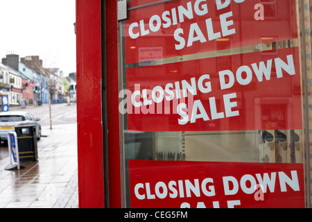 closing down sale signs in a small high street business window in the uk falling sales in british high st shops - Stock Photo