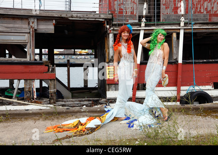 Two mermaids in front of an old wreck of a ship in the old part called Refshaleøen in the Port of Copenhagen, Denmark. - Stock Photo