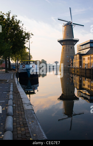 Mill and ship with reflection in water at sunrise - vertical image - Stock Photo