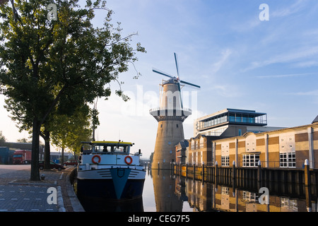 Mill and ship with reflection in water at sunrise - horizontal image - Stock Photo
