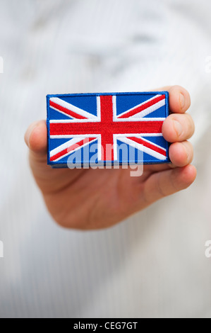 Hand holding a Union Jack flag embroidered patch - Stock Photo