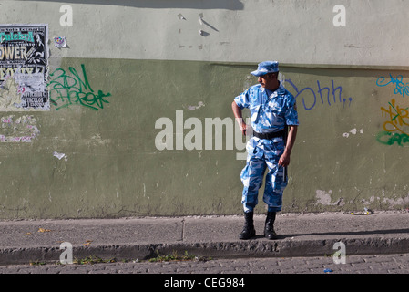 A Guatemalan military man in blue and white uniform stands on the sidewalk in Latacunga, Ecuador. - Stock Photo