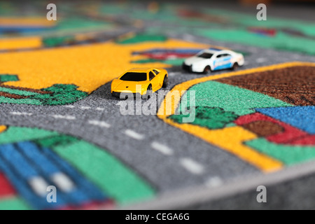 Toy Cars On A Rug. Police Car Chasing A Lamborghini   Stock Photo
