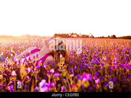 Beautiful young woman lying on a flowery meadow - Stock Photo