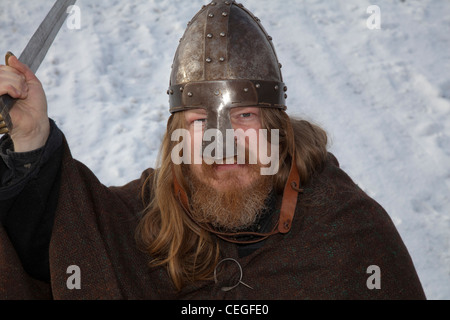 Viking re-enactor, with beard & long hair wearing Helmet and carrying sword at the 27th Annual JORVIK Festival in - Stock Photo