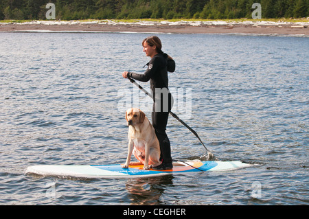 Woman & dog Standup Paddle Boarding off Kruzof Island, Southeast Alaska - Stock Photo