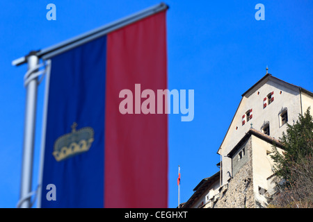 The official flag of Liechtenstein in the foreground and Vaduz castle in the background, Liechtenstein - Stock Photo
