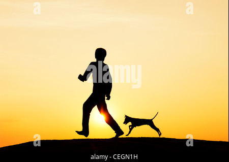Silhouette of young Indian boy running and playing with his puppy. India - Stock Photo