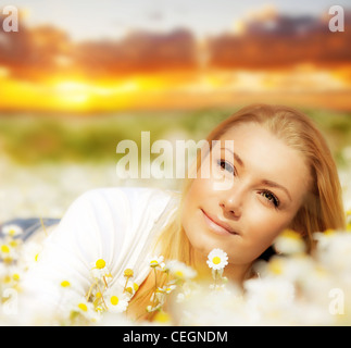 Beautiful woman enjoying daisy field at sunset, nice female lying down in the meadow of flowers, pretty girl relaxing - Stock Photo