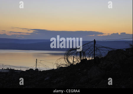 Golan Heights. Barbed wire and view of the Sea of Galilee from the foothill of Mount Susita - Stock Photo