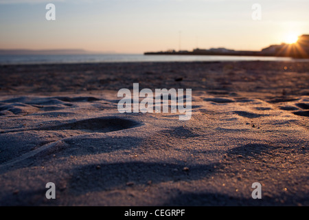 Frost on Weymouth beach as sun rises over the bay. - Stock Photo