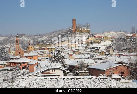 Houses, churches and ancient castle tower in small town of Corneliano D'Alba on snowy day in Piedmont, Italy. - Stock Photo