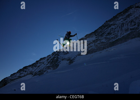 Male skier leaping against clear blue sky - Stock Photo