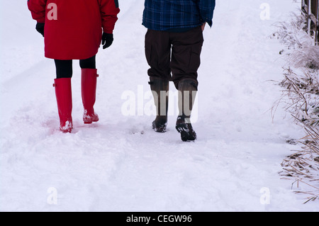 People Couple Rear View Of Walking Through The Snow Wearing Wellington Boots Winter UK - Stock Photo
