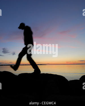Silhouette of man walking by a lake at night - Stock Photo