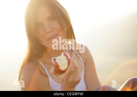 Beautiful young woman eating a juicy red apple in the beautiful golden light of the setting sun - Stock Photo