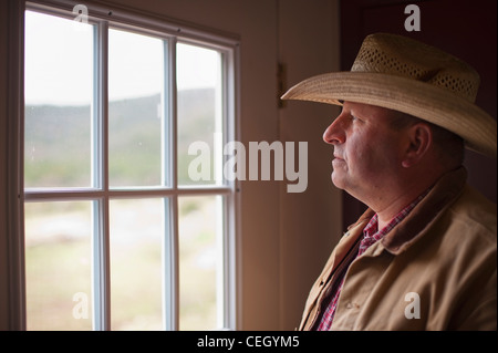 Old cowboy looking out of a window - Stock Photo