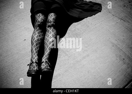 Woman wearing tights, laying on pavement. Black and white. - Stock Photo