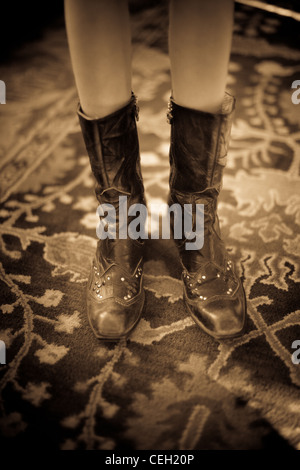 Close up of a girl wearing cowboy boots, sepia - Stock Photo