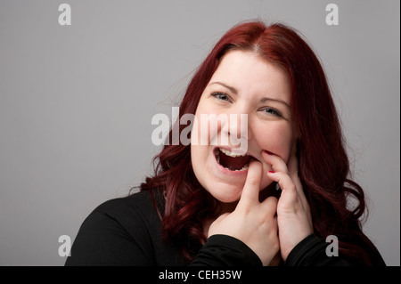 A auburn haired caucasian woman suffering from toothache painful teeth or sore gums gum mouth oral health tooth - Stock Photo