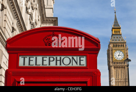 Close view on traditional red telephone box with Big Ben clock tower behind Westminster London UK - Stock Photo