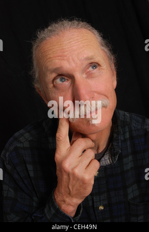 Adult man with hand on chin, looking up and to the left as if in thought.  On black background. - Stock Photo