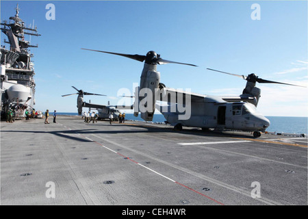 Marines and sailors unload gear brought aboard the USS Wasp by two MV-22B Ospreys from Marines with Marine Medium - Stock Photo
