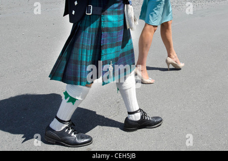 A man dressed up a Scottish kilt and a woman wearing a dress walks down the street. - Stock Photo