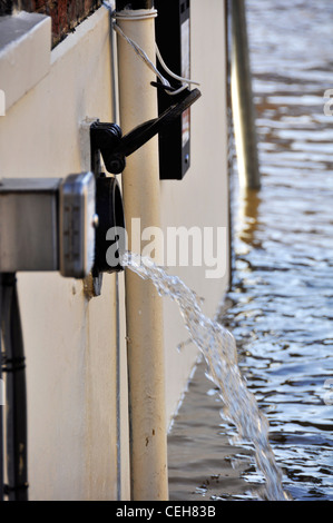 Closeup of flood water being pumped out of cellar after River Ouse has flooded its banks. - Stock Photo