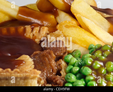 Close up of Steak Pie and chips with peas and gravy. A traditional British Dish - Stock Photo