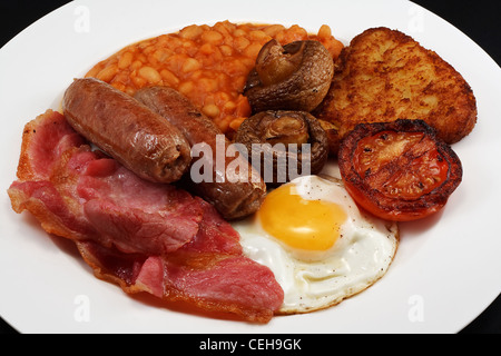 Typical fry up consisting of Sausage, bacon, egg, mushrooms, hash browns, beans and Fried Tomato - Stock Photo