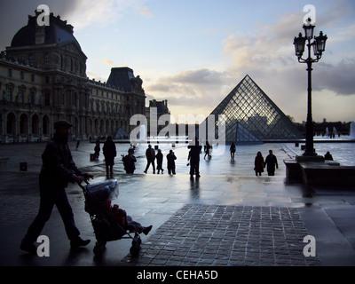 Silhouettes on a rainy day in Place du Carrousel du Louvre, Paris, France - Stock Photo