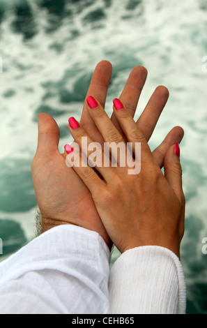 Men's and Women's tanned hands against the sea