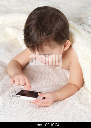 Two year old boy using an iPhone - Stock Photo