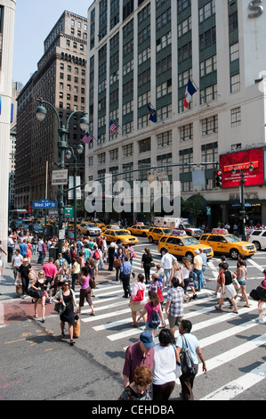 Pedestrians crossing road at West 34th Street, New York. on a Zebra crossing - Stock Photo