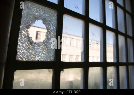 broken window hole glass shattered looking out horizontal - Stock Photo