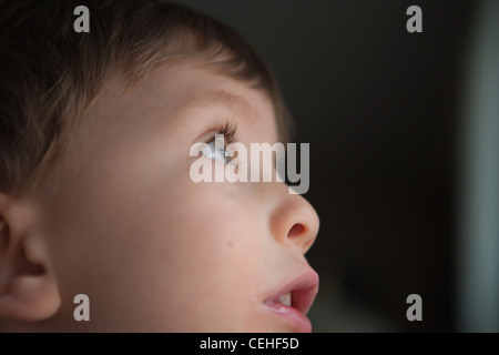 close up of two year old boy looking up through window, profile of face.
