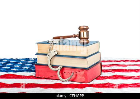 Gavel, law books and handcuffs resting on an American flag with a white background for placement of copy. - Stock Photo