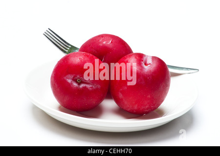 Three red plums on white background - Stock Photo