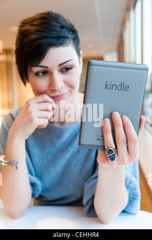 Young woman reading ebook on an Amazon Kindle, London, England, UK - Stock Photo