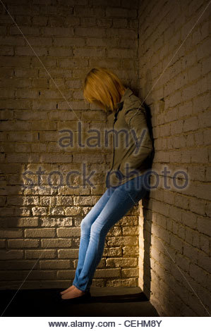 Unidentifiable teen girl standing leaning against a brick wall looking depressed with her face hidden. - Stock Photo