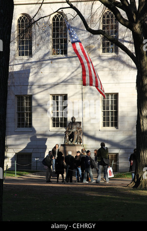 Tourists gathering in front of the famous statue of John Harvard on the campus of Harvard University in Cambridge, - Stock Photo
