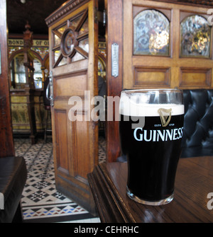 In the crown saloon bar Belfast with a pint of Guiness - Stock Photo