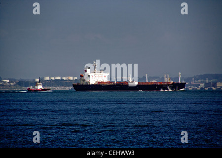 Accompanied by a tugboat, an ocean going oil tanker crosses San Francisco Bay. Note large 'No Smoking' sign on ship. - Stock Photo