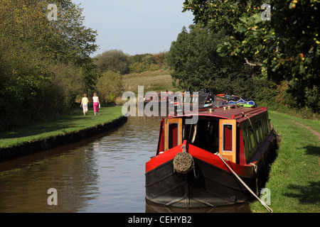 Canal boats on the Llangollen canal near Whitchurch, Shropshire UK, with people walking away from camera on the - Stock Photo