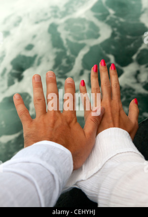 Men's and Women's tanned hands against the raging sea