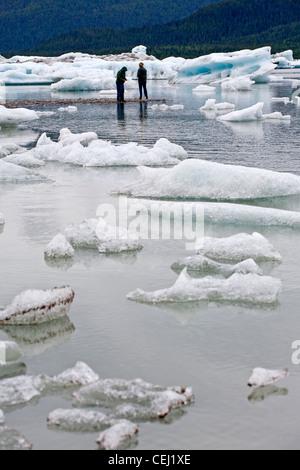Couple contemplating the icebergs from the Mendenhall Glacier. Mendenhall Lake. Juneau. Alaska. USA - Stock Photo